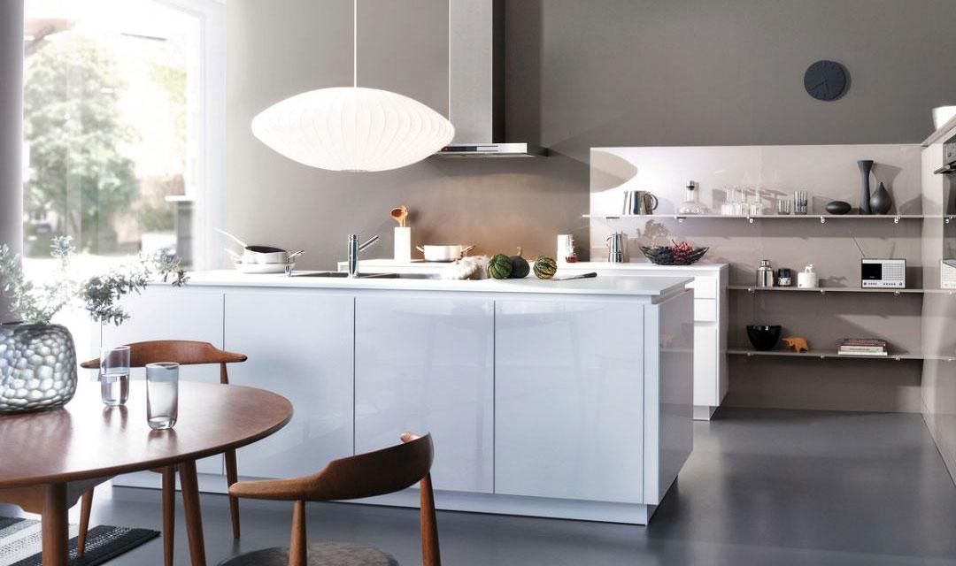 """Une conception de cuisine claire, conviviale et ouverte avec beaucoup d'espace pour vivre et travailler. La cuisine est guidée horizontalement par les façades sobres et lisses avec leur prise de main à la couleur coordonnée. Le nouveau concept sans poignée CONTINO est ici présenté avec deux programmes actuels LEICHT, la CHIARA-BG-C avec ses façades laquées brillantes en couleur """"firn"""" combinées avec les façades brillantes en acrylique de la LUNA-AG-C dans un ton clair """"gris sable"""". Les deux programmes se distinguent grâce aux nouveaux traitements sans joint des chants. Un critère décisif pour la plus grande qualité et un design exigent. Pour ce faire, LEICHT utilise une technologie laser des plus modernes qui permet de rendre invisible le joint entre le matériau de façade et le chant latéral."""