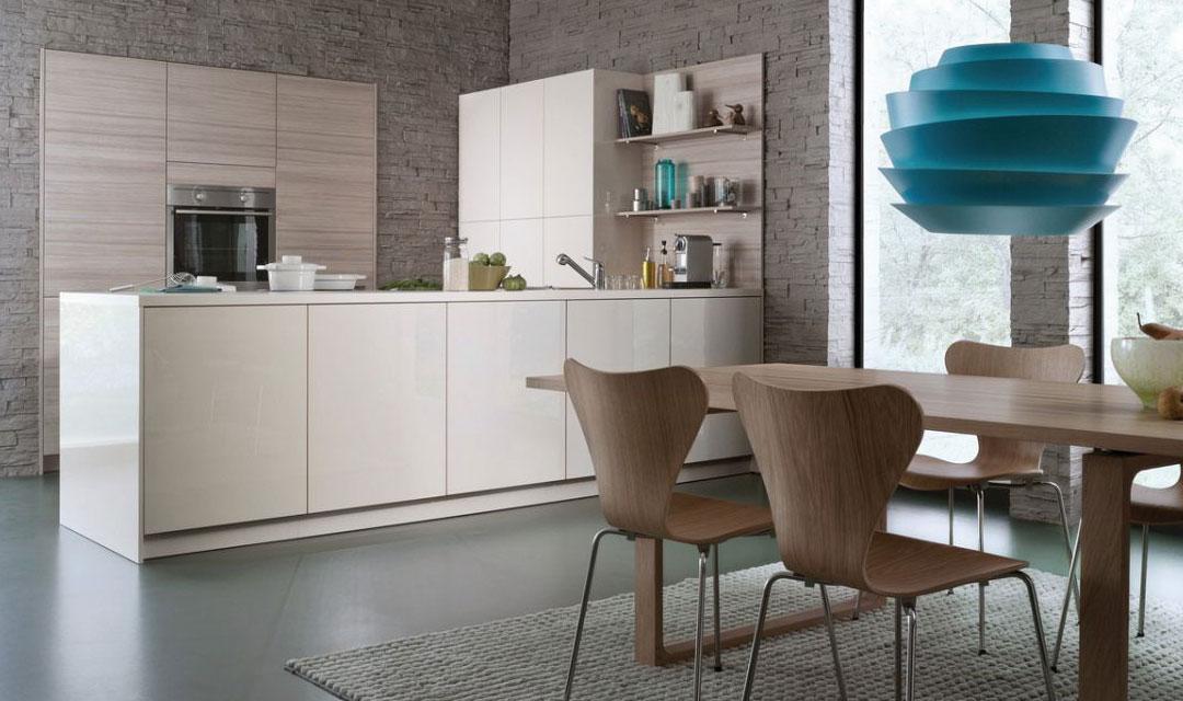 Par exemple des façades acryliques en blanc magnolia brillant et un décor en bois de mélèze de montagne en mat naturel. Le meuble étagère avec panneau arrière et les meubles bas sans poignée sont accessibles par le côté espace repas. Le demi-îlot s'ouvre sur la cuisine de trois côtés. Un plus dans la planification : les joues latérales et le plan de travail affleurant forment un bloc îlot fermé. Les meubles suspendus sans poignée avec système Sésame sont disposés pour créer une surface tranquille.