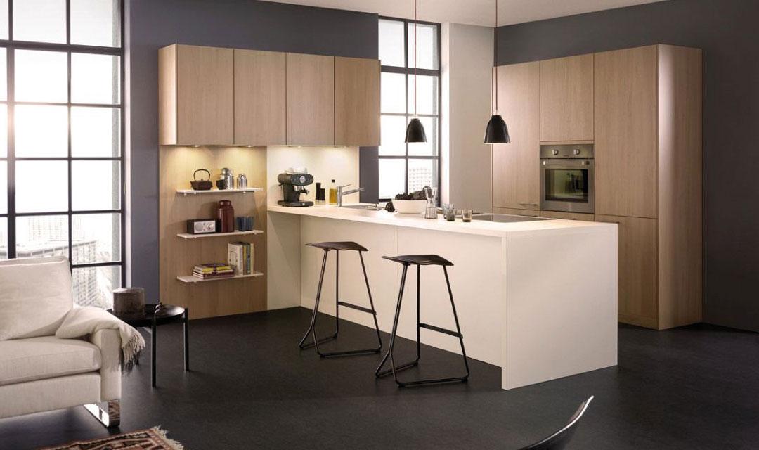 Confort et fonctionnalité ne sont pas incompatibles. Un décor bois en hêtre clair combiné avec des façades en magnolia blanc, un éclairage agréable, une ouverture sur la salle de séjour et l'intégration d'éléments de salon dans la cuisine sont ici les choix qui ont été faits. L'îlot définit la transition de l'espace de travail vers l'espace de séjour. Des joues de la même couleur et un plan de travail affleurant donnent à l'îlot son aspect compact en forme de bloc. Les meubles suspendus sans poignée avec les lampes LED montées surplombent l'îlot et l'étagère ouverte.