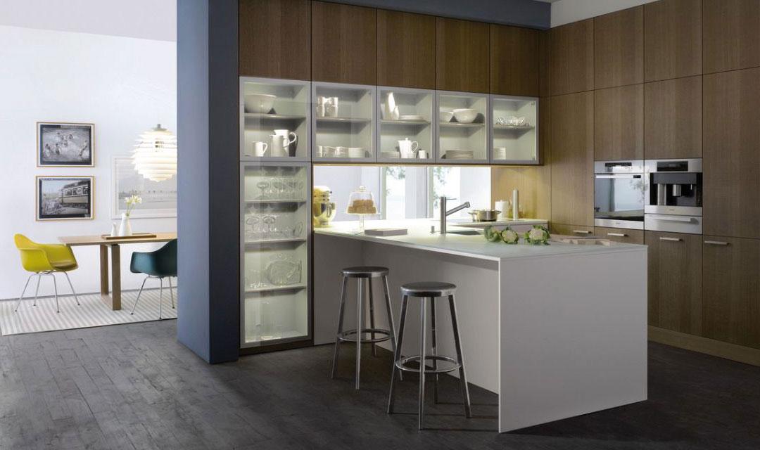 """Un trio de matériaux harmonieux composé de chêne cuivre particulièrement naturel avec ses marques de coupes artificielles brutes, d'un stratifié Resopal en mat satiné magnolia et de verre à l'intérieur et à l'extérieur des meubles, forme les façades de la cuisine. La cuisine est une partie de l'architecture de la pièce, elle sépare les espaces et s'ouvre sur le salon en même temps. Un plan de travail en verre mat-satiné conçu pour la cuisine est utilisé ici. Le dessous du plan est laqué d'une teinte RAL-""""classic"""" en harmonie avec les façades. Les meubles intégrés dans les murs et à hauteur de plafond offrent beaucoup d'espaces de rangement."""